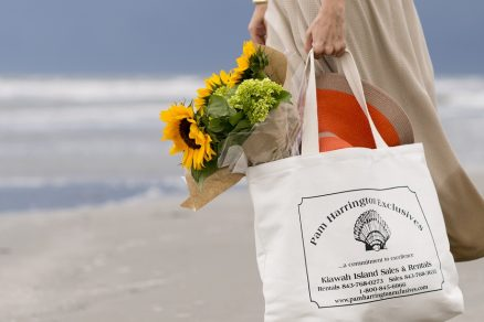 Woman holding a Pam Harrington Exclusives branded tote with sunflowers