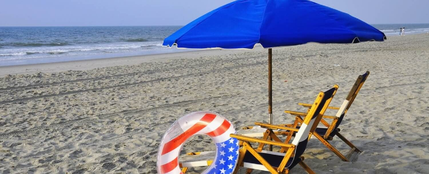 Beach chairs - umbrella - flag colored float ring on beach