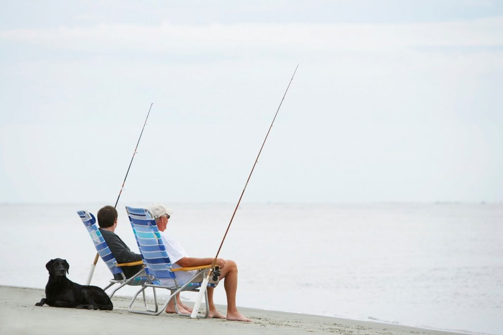 Dog lying by two men sitting on chairs and fishing on beach seabrook island