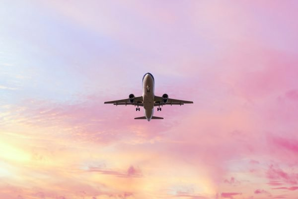 "Landing airplane on the pastel colored sky background. Sunset sky in the pink and blue colors ""n"