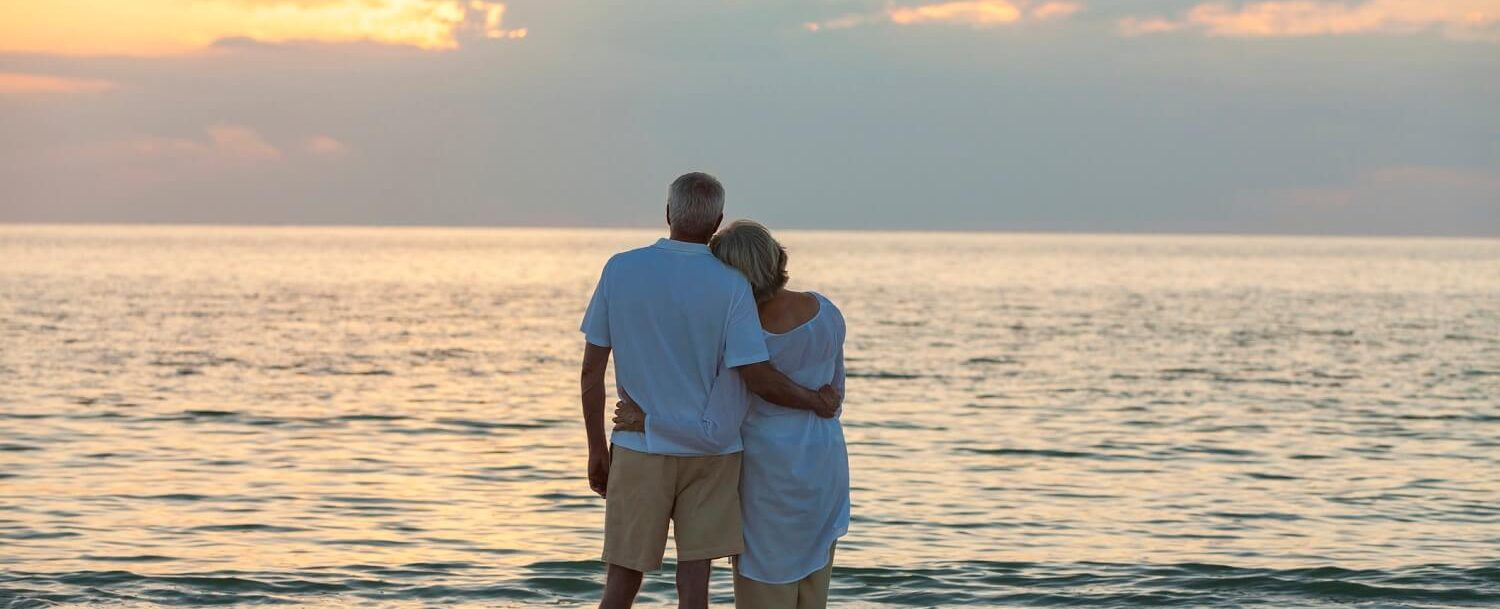 Retired Couple Looking at Sunset from the beach