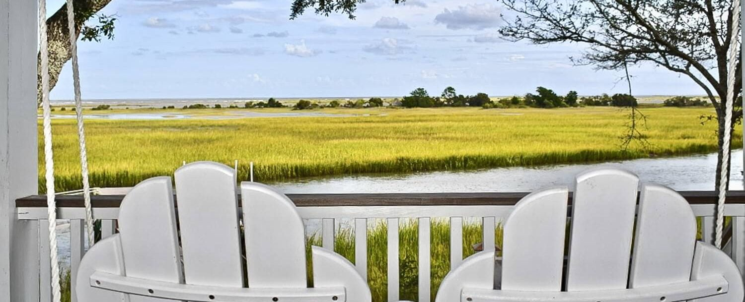 Wine Time - Backs of two white wood chairs in front of the marsh
