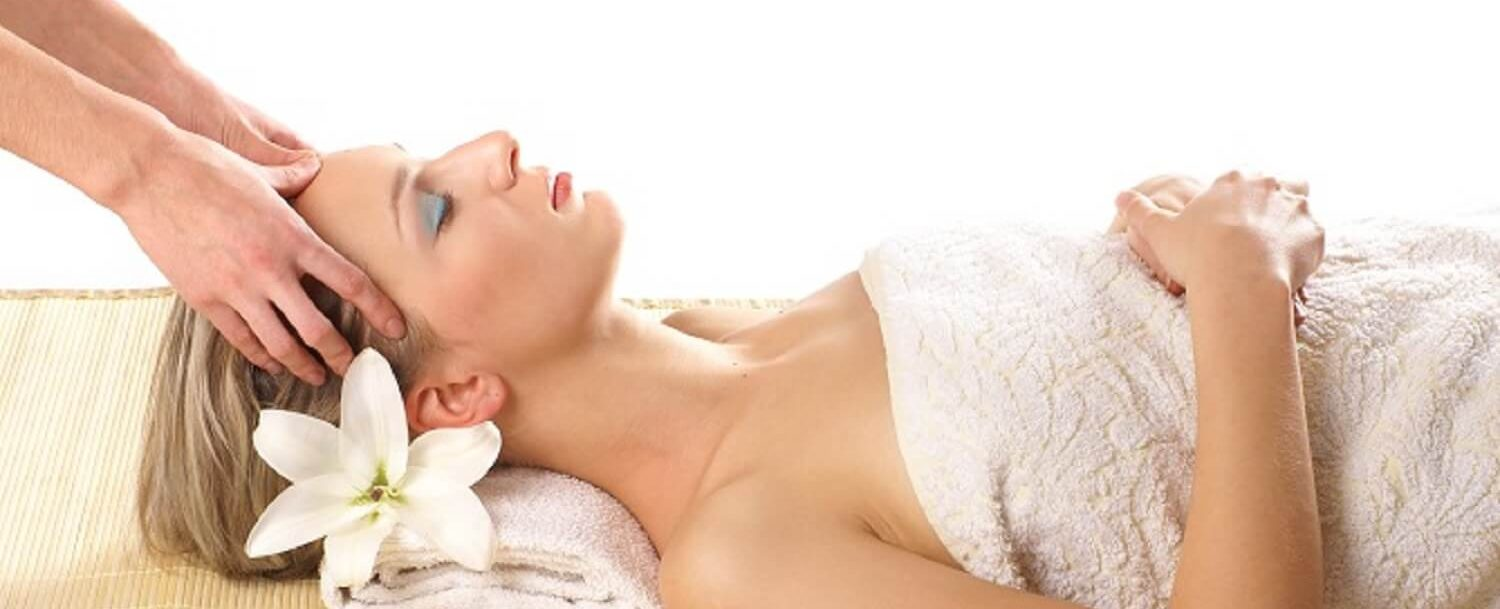 Woman laying down in towel getting head massaged