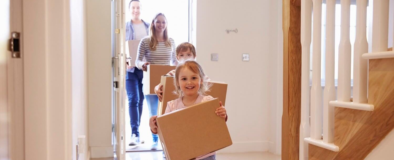 family carrying boxes to move into new house