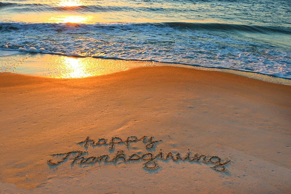 Happy Thanksgiving written in the sandy coast during a beautiful sunrise.